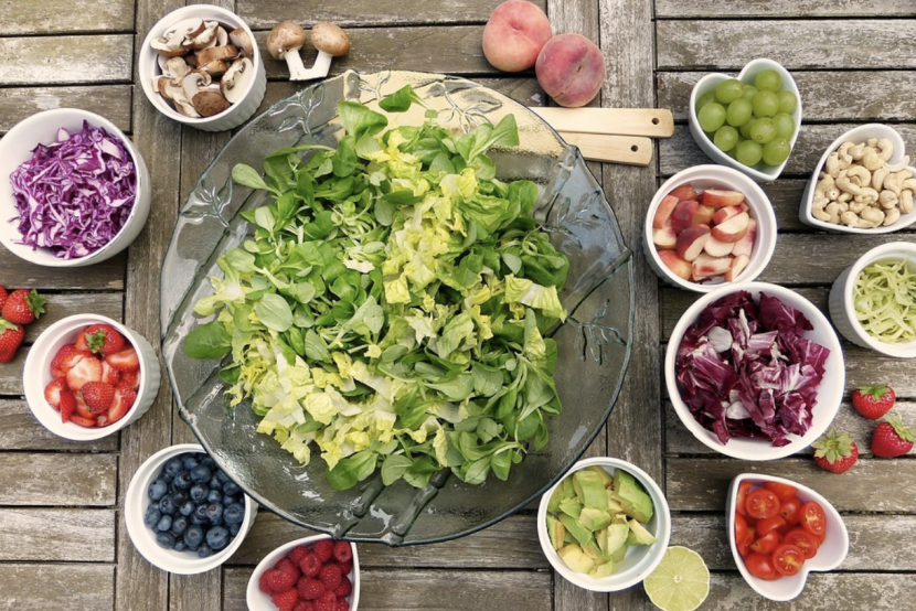 A bowl of lettuce in the center of various fruits, vegetables, and other healthy components.