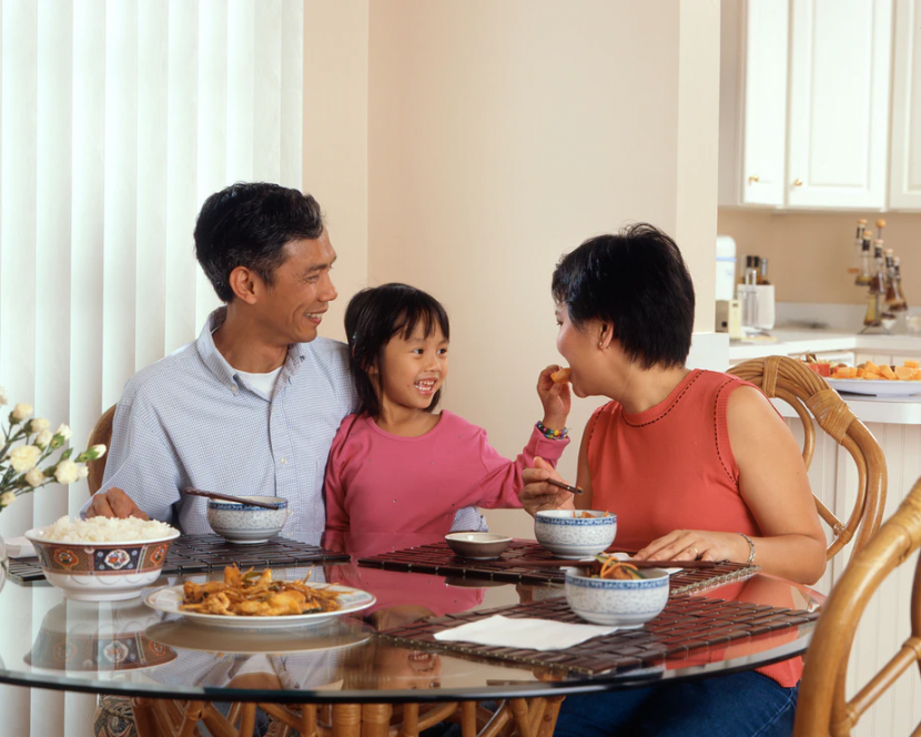 A child with diabetes eating a healthy meal with her parents